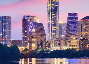 The skyline of Austin, Texas is reflected in a body of water, with a blue, pink and yellow sunset sky behind the illuminated buildings