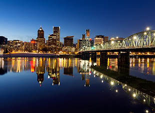 Landscape view of the illuminated Portland, Oregon downtown - with buildings and a bridge - reflecting over water at night