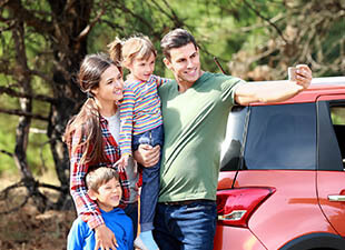 A happy family taking a selfie next to a red car