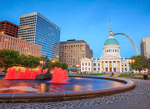 An orange-lit fountain is pictured in the foreground, with bulidings and part of the Arch of downtown St. Louis, Missouri in the background at dusk.