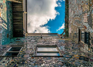 A view from below the largest work created by mosaic artist Isaiah Zagar made of found objects shines in the daylight at Magic Garden Philadelphia.
