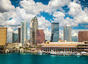 The Tampa, Florida, skyline shines under a blue afternoon sky.
