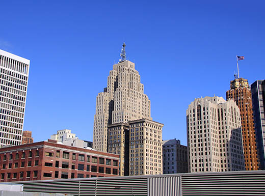 Skyscrapers in downtown Detroit, MI on a sunny day with a bright blue sky in the background