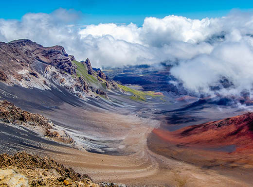 Beautiful colors seen at a massive volcanic crater on Maui, Hawaii on a sunny day with low, white, puffy clouds.