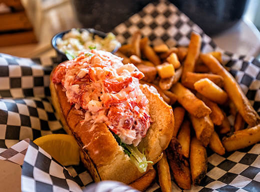Maine Lobster Roll With Fries On Checkered Parchment Paper At The Cape Cod Fish Co