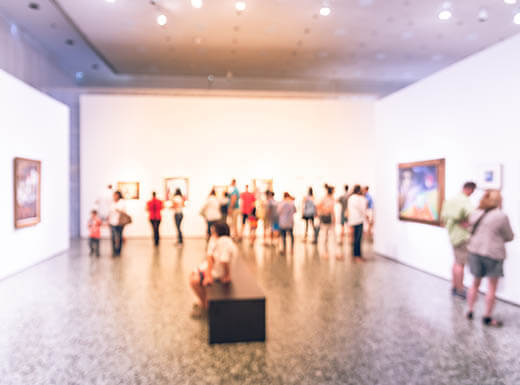 crowd of people viewing art at a gallery