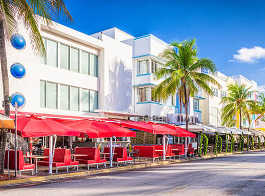 Miami beach street lined with palm trees and restaurant patios.
