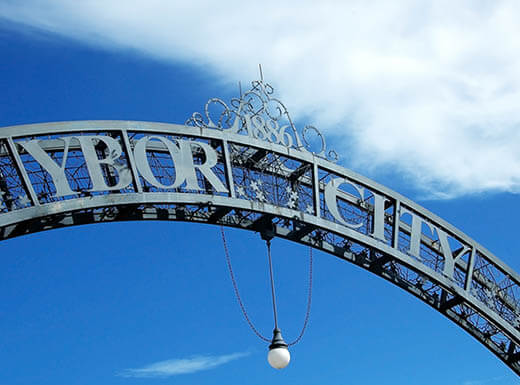 An Ybor City arched sign sits beneath a blue sky in Tampa, Florida during the day.