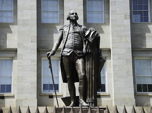 The grey statue of George Washington stands outside an office building in downtown Raleigh, North Carolina on a warm morning.