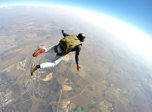 Man wearing green parachute and black helmet is seen above the Earth as he skydives from plane over San Jose, California on a clear day