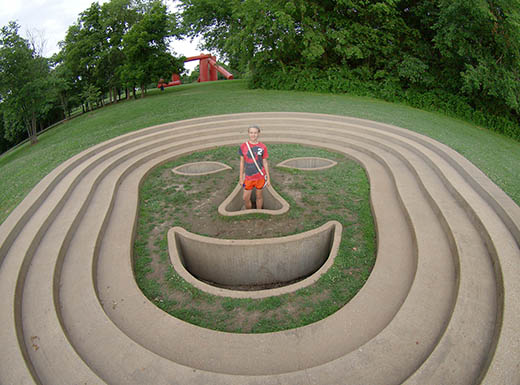 A girl in a t-shirt and shorts stands inside the triangle shaped nose of an in-ground face sculpture surrounded by green grass and trees in St. Louis, MO on a cloudy summer day