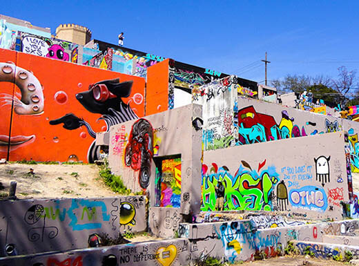 Numerous outside concrete walls with graffiti on them are pictured at the HOPE Outdoor Gallery in Austin, Texas on a sunny afternoon.