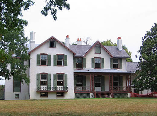 Exterior front view of President Lincoln's Cottage and trees in Washington D.C., a white home with green shutters and brown wooden deck