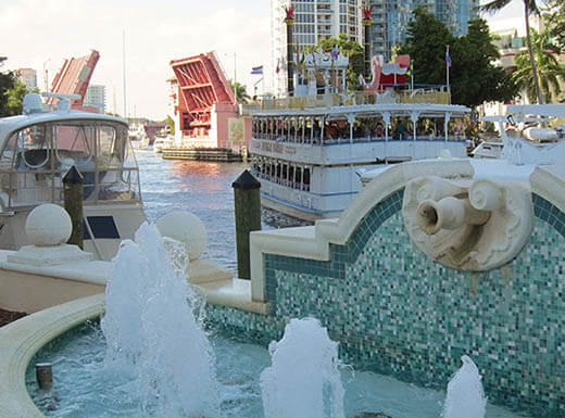 View of the river front, with boats seen on the water of the New River behind a water fountain with bright turquoise tiling from the Riverwalk and a red drawbridge in the distance in Fort Lauderdale, Florida in the late afternoon