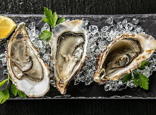 Oysters served on stone plate with ice with green parsley and a lemon wedge on a black table at Blue Pointe Oyster Bar and Seafood Grill in Fort Myers, Florida, restaurant