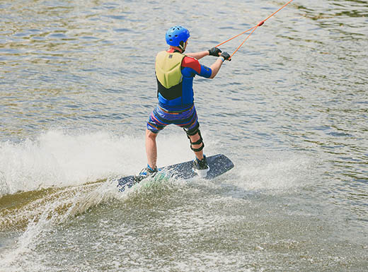 A young man in a blue and yellow life vest and blue helmet wakeboards using an overhead cable on a hot summer day at the Wake Nation Adventure Park in Houston, Texas.