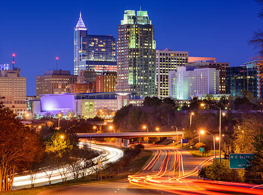 The streaks of cars going down a road are seen in the foreground with the bright lights of downtown Raleigh, North Carolina in the background on a bustling summer night.