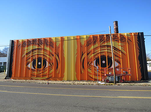 Along the side of a road, an orange and yellow painted mural features two large eyes with eyebrows on an industrial building under a blue morning sky in St. Louis, Missouri