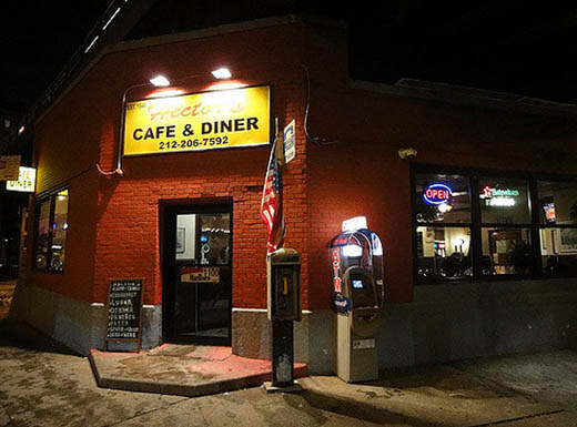 A yellow sign hangs above the entrance to Hector's Café & Diner with a flag next to the black door and painted red brick wall in Chelsea at night in New York City