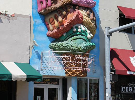 The exterior of Azucar ice cream parlor with 3D images of scoops of ice cream atop a cone is hit by the afternoon sun on a bright day in Miami