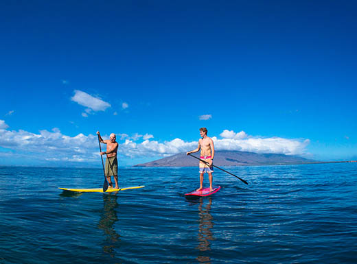 A father and son paddleboard together under a perfect blue afternoon sky in Maui.