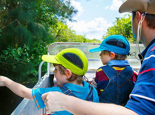 A father and his two sons enjoy an airboat tour of the Everglades on a sunny afternoon.