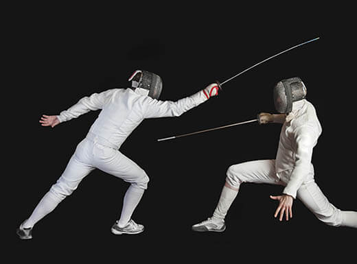 Two men in traditional fencing attire lunge while fencing against black background at the Fencing Center in San Jose, California