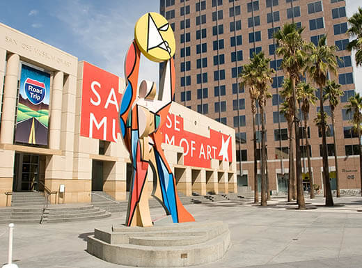The exterior of San Jose Museum of Art, displaying a colorful and abstract sculpture in downtown San Jose, CA, on sunny day