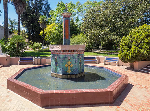 A brick fountain with blue and yellow tiles outside Rosicrucian Egyptian Museum in San Jose, CA