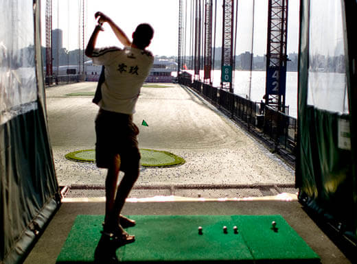 Silhouette of man hitting golf balls near the Hudson River during the day at New York City's Chelsea Piers