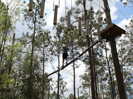 Visitor walking between trees at Orlando Tree Trek Adventure Park