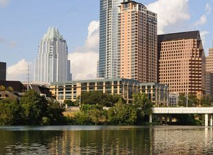 The skyline of Austin, Texas is pictured with its reflection in the Colorado River, and a blue sky with white fluffy clouds in the background on a bright, sunny afternoon.