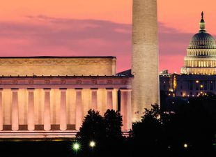 The Washington Monument stands illuminated, high above the Washington, D.C. skyline with an orange and pink sunset and the Capitol building in the background on a spring evening.