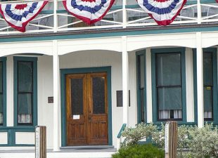 View from the water of Stranahan House Museum, a white 2-story house with gray shutters, wrap around porch and American Flag out front sits right on the water, oldest building in Fort Lauderdale, Florida
