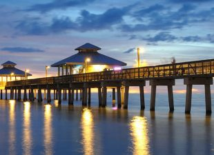Lights reflecting in the water at Fort Myers, Florida, Pier at the end of sunset, with just a sliver of orange light showing in the darkening sky