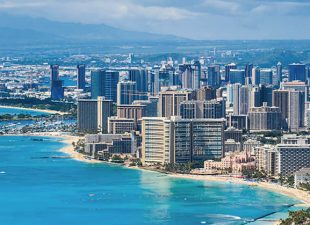 Aerial view of the city of Honolulu, Oahu in Hawaii and the coastline along the beautifully blue ocean on a clear, bright sunny day