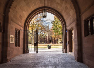 A view of Phelps Gate at Yale University leading towards the green campus courtyard with students in the background on a bright afternoon.