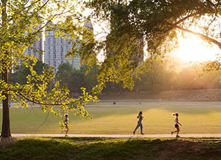 Sunny day, people jogging through Piedmont Park in Atlanta, Georgia