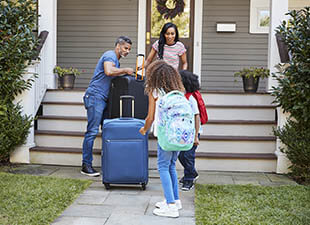 A family of four carries luggage down the front steps of a house on a sunny morning.