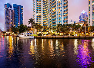 Fort Lauderdale, Florida, cityscape from the water at dusk show colorful lights reflected on the water and palm trees and boats along the shore line.