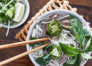 Overhead photo of bowl of Vietnamese beef pho with chopsticks, Thai basil, cilantro and jalapeños next to a bowl of toppings on a wooden table in a restaurant in Houston, Texas