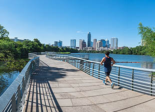 A runner outdoors in tank top and shorts passes by Lady Bird Lake and green trees on the Ann and Roy Butler Hike and Bike Trail under a blue afternoon sky with the skyline of Austin, Texas in the distance.