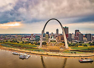 The famous Gateway Arch is pictured high above the St. Louis, Missouri skyline, with the Mississippi River in front and a cloudy blue and orange sunset sky in the background