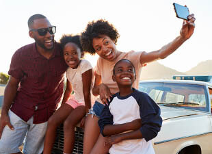 A family poses for a selfie next to a parked car as the sun sets near mountains on a bright evening.