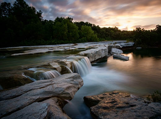 Sunrise over rocks and water at McKinney Falls State Park in Austin, Texas.