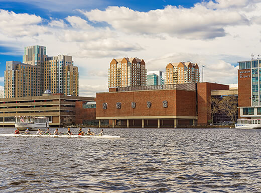 View from water of Museum of Science in Science Park and Charles River on partly cloudy day.