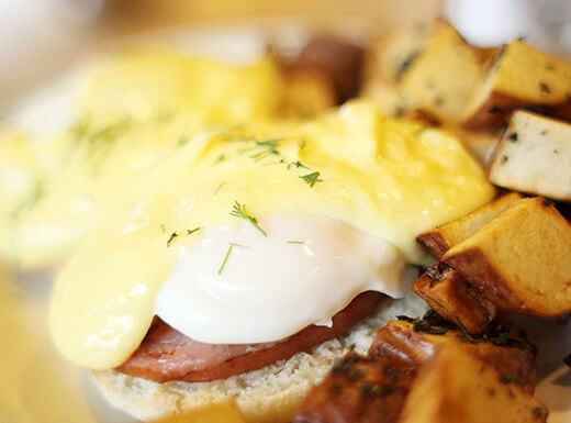 Close up view of eggs Benedict on a white plate.