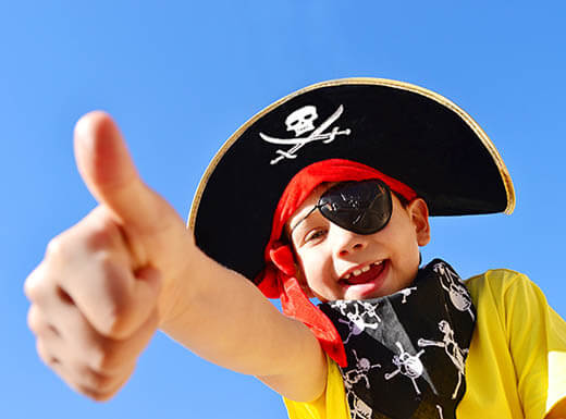 Young boy dressed up as a pirate gives thumbs up to camera under blue sky