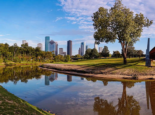 A panoramic view of downtown Houston, as seen from Buffalo Bayou Park on a sunny day.