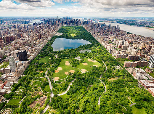 Aerial view of Central Park and surrounding Manhattan neighborhoods on a partly cloudy day.